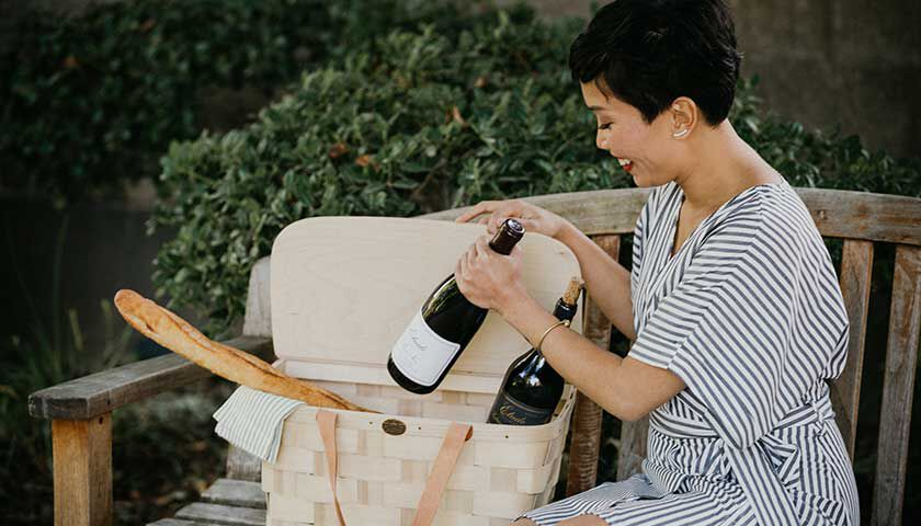 woman with a picnic featuring etude pinot noir