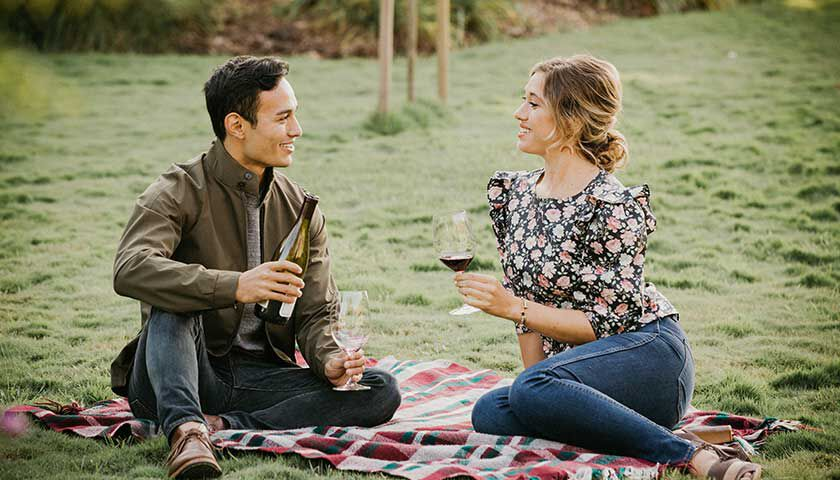 couple enjoying a picnic on the lawn at our winery in carneros, napa