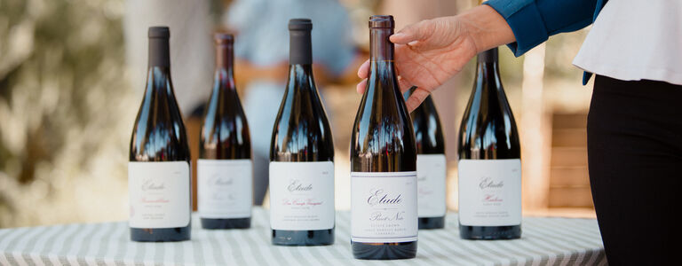 a table of etude pinot noir ready for a wine club tasting