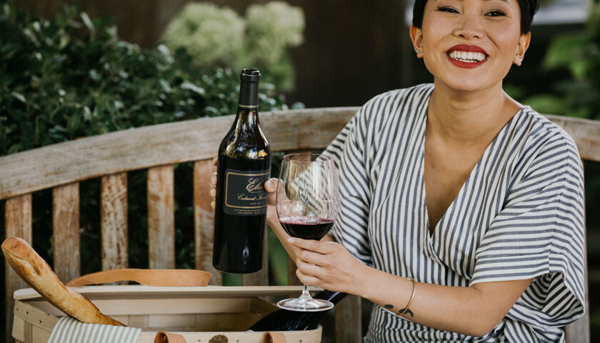 woman enjoying a glass of etude cabernet sauvignon with her picnic